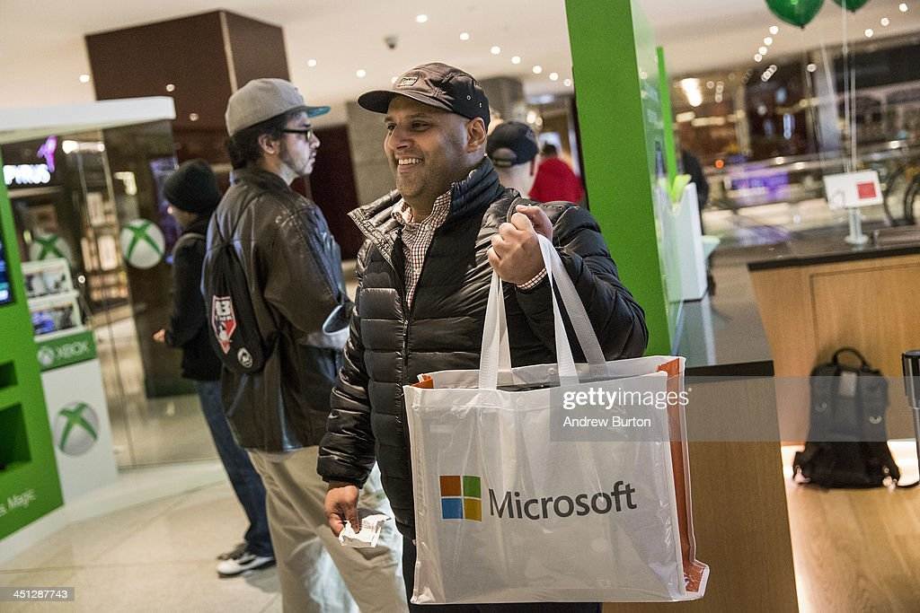 A man poses for a photo after purchasing an XBox One - a new video game console and home entertainment system made by Microsoft- from a Microsoft 'pop-up shop' at the Time Warner Center at Columbus Circle on 22, 2013 in New York City. The X Box One arrives just in time for the holiday season, and will be competing against the Sony Playstation Four, which came out last week.