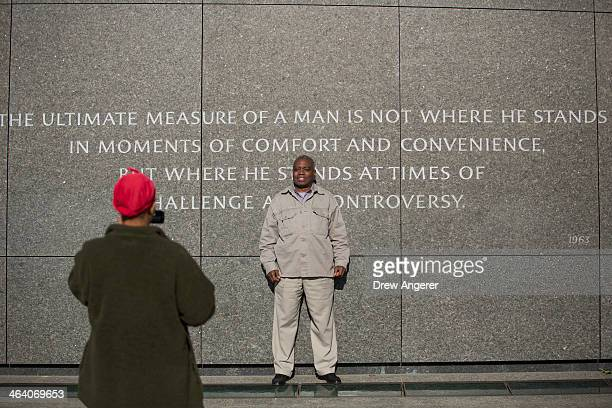 A man poses for a photo in front of a quote from Dr King at the Martin Luther King Jr Memorial January 20 2014 in Washington DC Americans marked the...