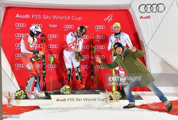 TOPSHOT A man poses for a photo while S econd placed Henrik Kristoffersen of Norway Winner Marcel Hirscher of Austria and third placed Daniel Yule of...