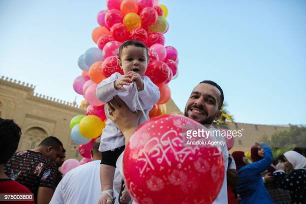 A man poses for a photo with his child after performed Eid alFitr prayer at MosqueMadrassa of Sultan Hassan in Cairo Egypt on June 15 2018 Eid alFitr...