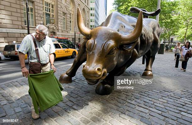 A man poses for a photo with the Wall Street bull sculpture between Broadway and Exchange Place in the Financial District of New York US on Wednesday...