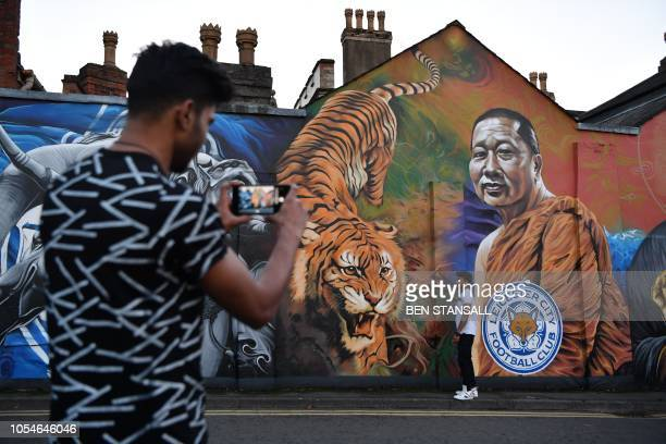 A man poses for a photograph against a mural showing Leicester City Football Club's Thai chairman Vichai Srivaddhanaprabha near De Montfort...