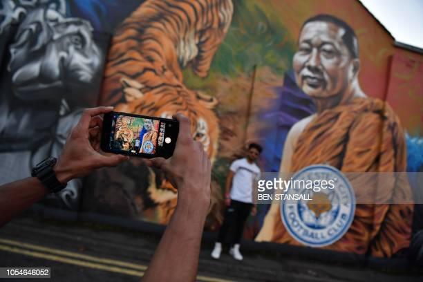 TOPSHOT A man poses for a photograph against a mural showing Leicester City Football Club's Thai chairman Vichai Srivaddhanaprabha near De Montfort...