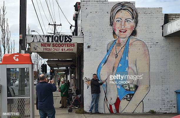 A man poses for a photograph in front of a mural of Democrat US presidential nominee Hillary Clinton clad in a swimsuit bearing the colours of the US...