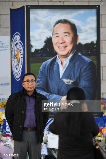 A man poses for a photograph in front of a portrait of Leicester City Football Club's Thai chairman Vichai Srivaddhanaprabha who died in a helicopter...