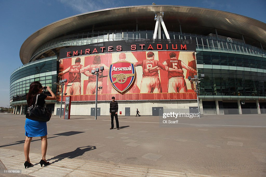 A man poses for a photograph in front of Arsenal Football Club's Emirates Stadium on April 11, 2011 in London, England. American businessman Stan Kroenke's company 'Kroenke Sports Enterprises' has increased its shareholding in Arsenal to 62.89% and will make an offer for a full takeover of the club. Kronke first purchased 9.9% of Arsenal shares in 2007. Today's deal values the Premier League club at 731m GBP.