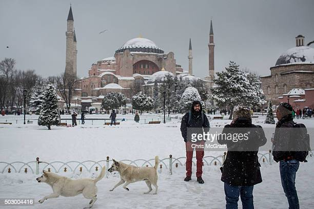 A man poses for a photograph in front of the Hagia Sophia during a heavy snow storm on December 31 2015 in Istanbul Turkey The city has prepared more...