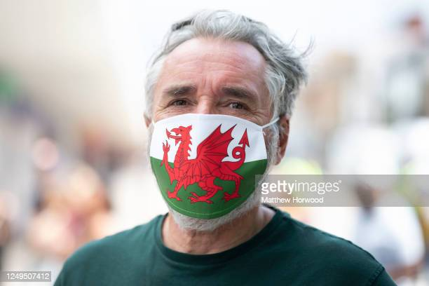 A man poses for a photograph wearing a surgical mask with a Wales flag design on June 13 2020 in Barry United Kingdom Wales First Minister Mark...