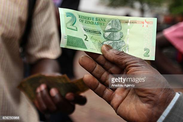 A man poses for a photograph with new banknotes as Zimbabwe Central bank launches new banknotes due to economical crisis in the country and...