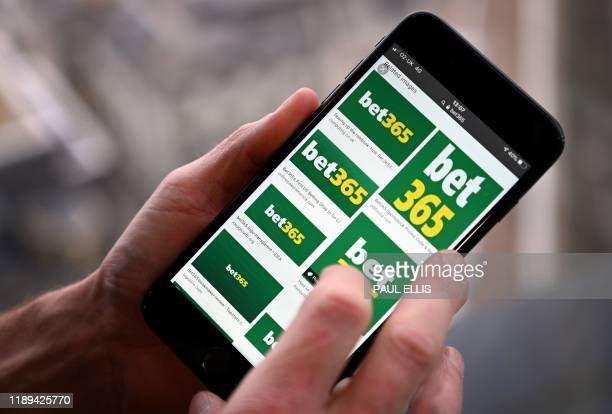 Man poses for a photograph with the logo for online gambling website Bet365 displayed on a smartphone, in London on December 18, 2019. - Denise...