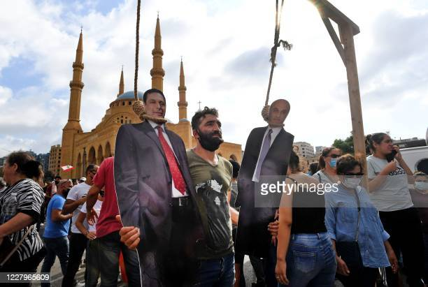 Man poses for a picture with a cardboard cut-out of Lebanon's Prime Minister Hassan Diab and Lebanese Forces executive chairman Samir Geagea hung by...