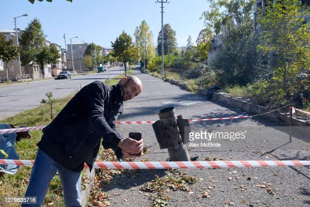 Man poses for a selfie in front of an unexploded missile which has lodged in the pavement on October 12, 2020 in Shoushi, Nagorno-Karabakh. On the...