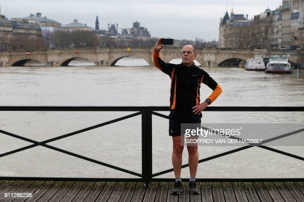 A man poses for a 'selfie' on a bridge over the swollen Seine river in Paris on January 28 2018 The swollen Seine rose even higher on January 28...