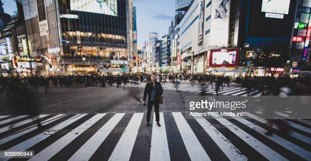 man poses for long exposure shibuya crossing - long exposure stock pictures, royalty-free photos & images