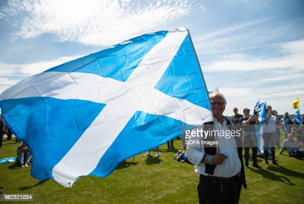Man poses for photographers cameras while holding a Scottish Flag. Thousands of Scottish independence supporters marched through Stirling and...