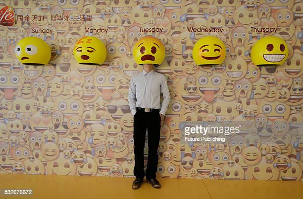 A man poses for photos with emoji hats fixed on a wall in a shopping mall in Guangzhou on May 18 2016 in Guangdong China Feature China / Barcroft...