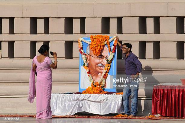 A man poses for the photograph near the portrait of Mahatma Gandhi on the occasion of his 144th birth anniversary on October 2 2013 in Noida India...