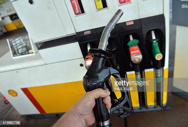 A man poses holding a petrol pump nozzle at a filling station in Birkenhead northwest England on May 19 2015 Britain's annual inflation rate sank...