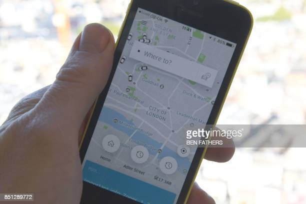 A man poses holding a smartphone showing the App for ridesharing cab service Uber in London on September 22 2017 London transport authorities...