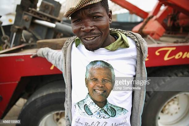 A man poses in a free tshirt which was one of many given away to the crowds as he waits for the funeral cortege of former South African President...