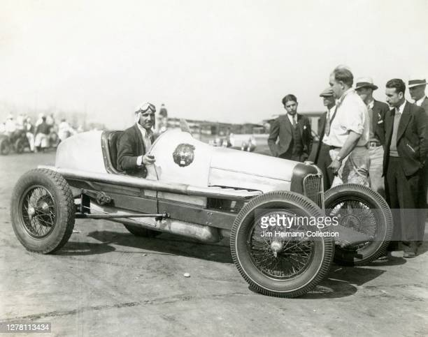 Man poses in a race car at the speedway with a crowd of people standing nearby, circa 1937.