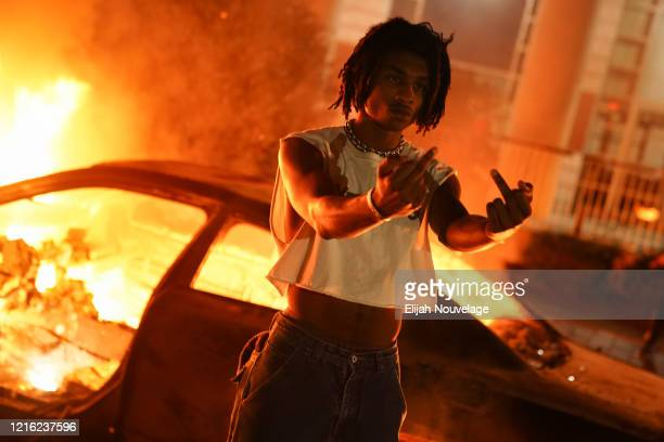 A man poses in front of a burning car during a protest on May 29 2020 in Atlanta Georgia Demonstrations are being held across the US after George...