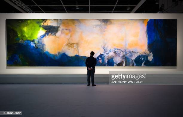TOPSHOT A man poses in front of 'JuinOctobre 1985' by Chinese painter Zao WouKi during a media preview for the piece at the Sothebys auction house...