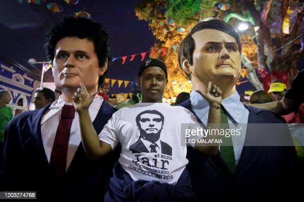 TOPSHOT A man poses next to giant puppets representing Brazilian President Jair Bolsonaro and Justice Minister Sergio Moro during a traditional...
