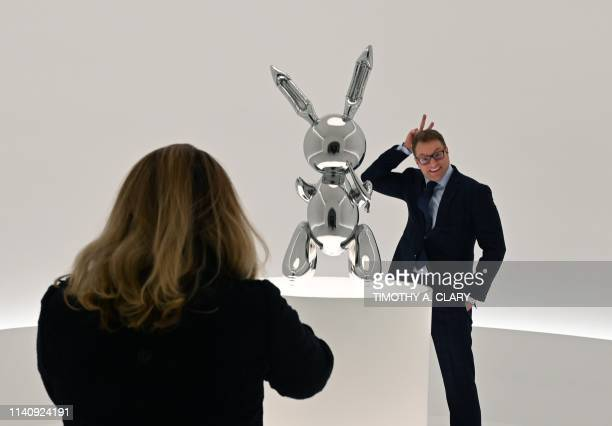 A man poses next to Jeff Koons' Rabbit from the Masterpieces from The Collection of SI Newhouse at Christie's New York press preview on May 3 2019 as...