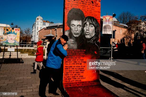A man poses next to the artwork 'David Bowie and Iggy Pop's Portraits' by French artist Jef Aerosol painted on a section of the Berlin Wall as part...