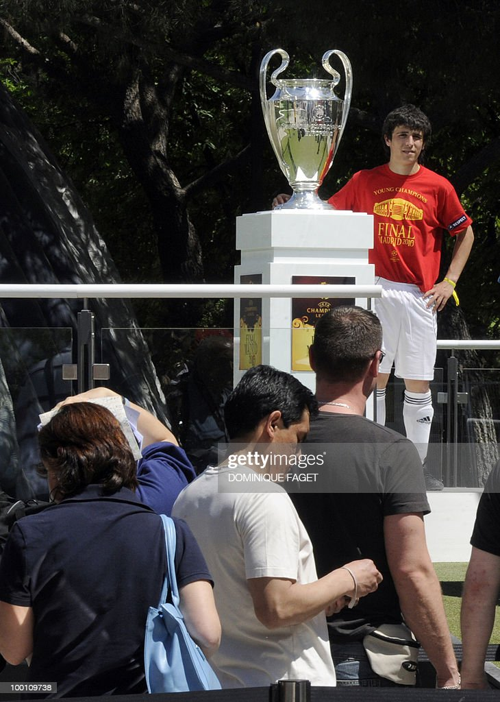 A man poses next to the UEFA Champions League Cup on display at the Retiro Park in Madrid on May 21, 2010 ahead of the UEFA Champions League final. Inter Milan will face Bayern Munich for the UEFA Champions League final match to be played at the Santiago Bernabeu Stadium in Madrid on May 22, 2010.
