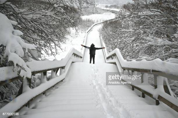 A man poses on a snow covered way after the first snowfall of the season in Lake Abant Nature Park in Bolu Turkey on November 21 2017