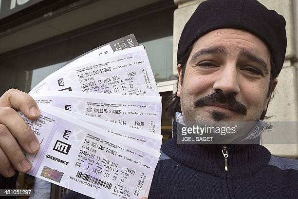 A man poses on March 28 2014 in Paris with tickets for a concert of British rock band The Rolling Stones scheduled on June 13 2014 at the Stade de...