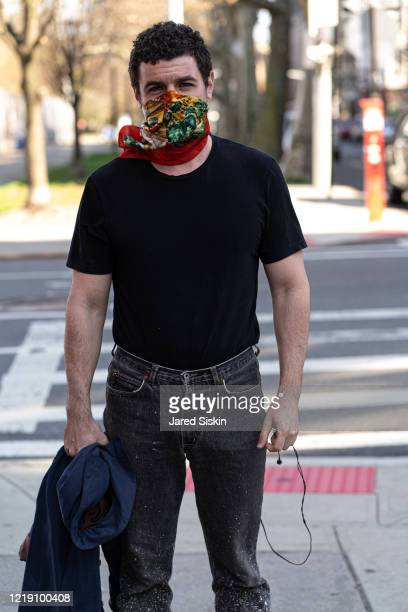 Man poses on the street wearing a red and yellow abstract art inspired bandana black tshirt and gray painters jeans on April 15 2020 in Williamsburg...