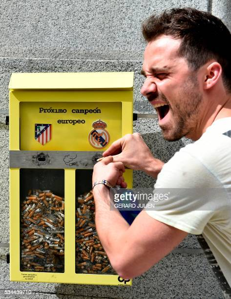 A man poses past an ashtray displayed by the City Council and shaped as a ballot box inviting the passerby to vote with their cigarette butt for the...