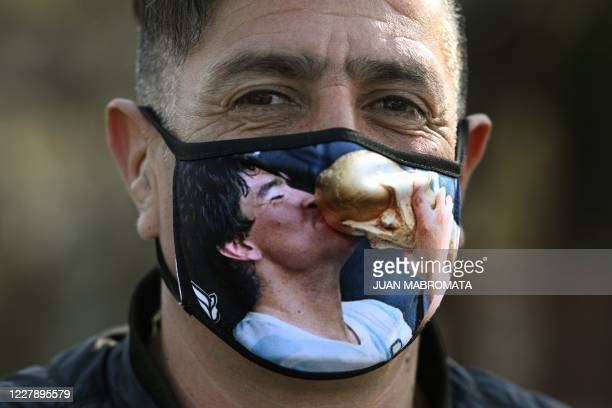 A man poses wearing a mask with the portrait of former Argentina's footballer Diego Maradona kissing the trophy of the FIFA World Cup Mexico '86...