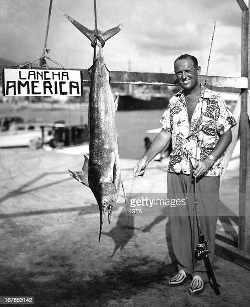 A man poses with a 44 pound blue marlin caught in Acapulco Mexico in October 1949