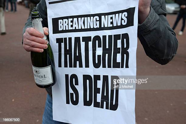A man poses with a bottle of cava and a sign displaying the message 'Thatcher is Dead' as other members of the public gather in George Square to mark...