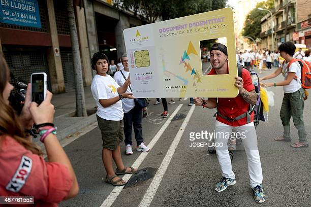 A man poses with a giant fake Catalan ID card during celebrations of Catalonia's National Day which recalls the final defeat of local troops by...