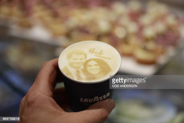 TOPSHOT A man poses with a 'Megharryccino' a Royal Weddingthemed coffee decorated with the faces of Britain's Prince Harryand Meghan Markle in a...