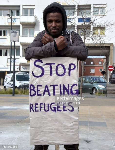 Man poses with a placard as he attends a gathering called by migrant aid collective Appel d'Air to protest against administrative policies on...