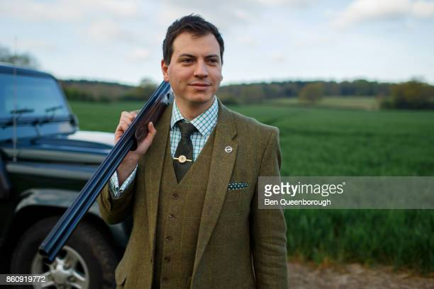 A man poses with a rifle at clay pigeon shoot