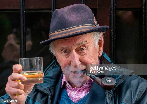 Man poses with a whisky outside Bittles bar in Belfast on October 16 as Northern Ireland is set to impose tighter coronavirus restrictions on the...