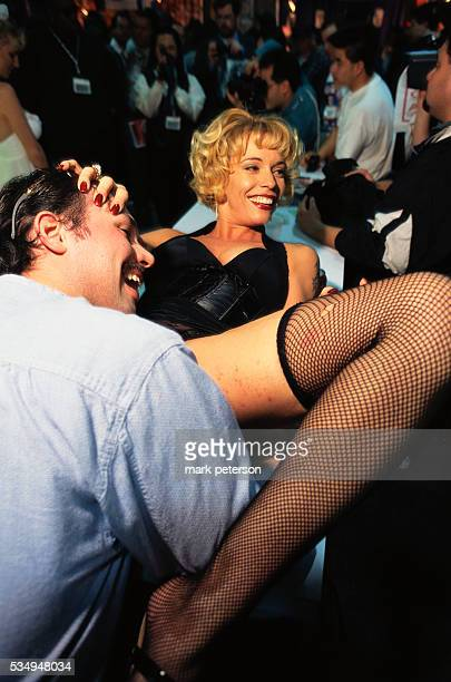 A man poses with an exotic dancer at AdultDex an adult entertainment convention that runs along with the Consumer Electronics Show in Las Vegas...