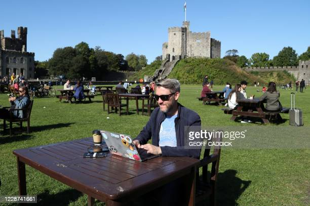 Man poses with his lap-top computer in the late summer sunshine in the grounds of Cardiff Castle in Cardiff, south Wales on September 27 during...