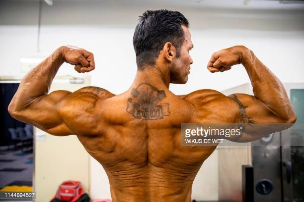 Man poses with his muscles flexed before the swimwear fitness competition at the Arnold Classic Africa, a multi-sport festival held at the Sandton...