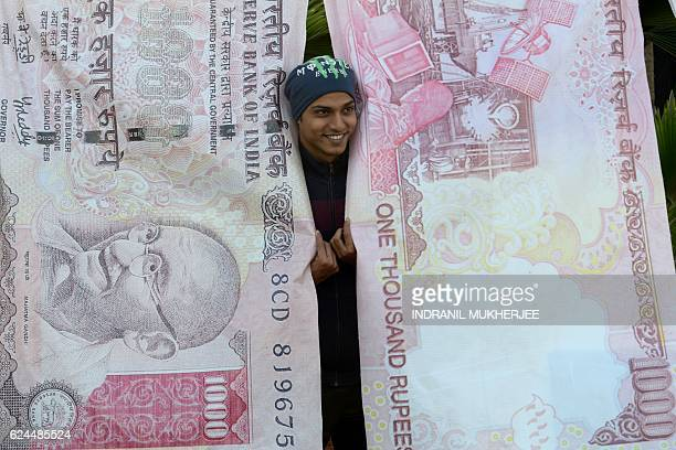 TOPSHOT A man poses with replica prints of the demonetised 500 and 1000 rupee notes as part of a street art exhibition in Mumbai on November 20 2016...