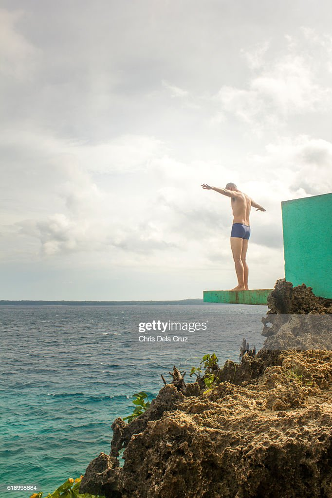 Man posing for a dive on a diving platform : Stock Photo