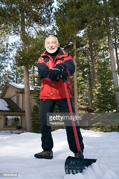 Man posing outdoors with snow shovel