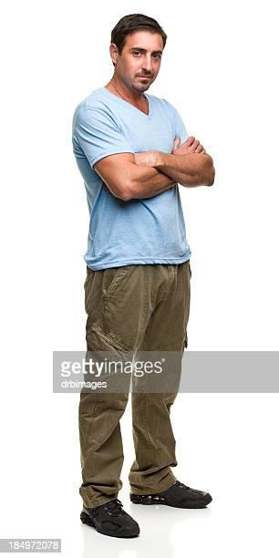 Hombre de pie con los brazos cruzados posando